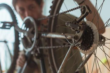 Bicycle mechanic repairing old mountain bike in workshop
