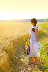 Young woman looking back at golden wheat field, holding sunflowers and american flag suitcase