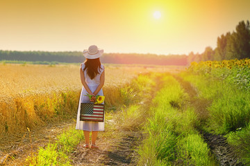Rear view of girl with american flag suitcase and sunflowers in arms, looking at sunset in golden wheat field