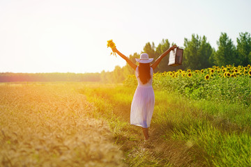 Rear view of happy, young woman with arms in the air holding american flag suitcase and sunflowers, walking in the golden wheat field