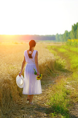 Rear view of happy, young woman holding hat and sunflowers, walking in the golden wheat field , sunset light