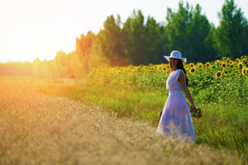 Young woman with sunflowers and american flag suitcase walking trough golden wheat  and sunflowers field, smiling at camera.Sunset light