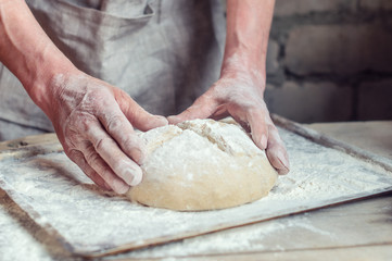 Deurstickers Bakkerij Wheat bread to the oven. The Baker's hands. Process the dough for wheat bread. Rustic style. Selective focus