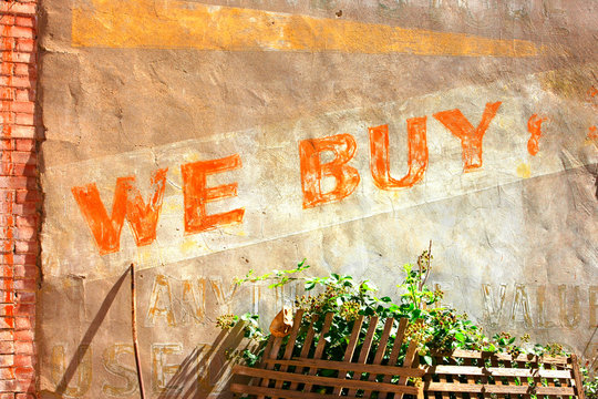 """Old paintwork painted on a wall saying """"We Buy"""" in downtown Bisbee, AZ"""