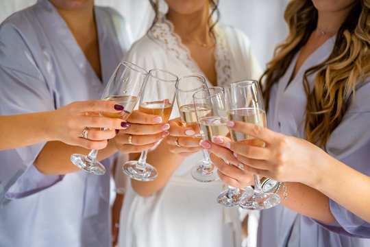 Girls in dressing gowns hold glasses of champagne at a bachelorette party at the hotel.