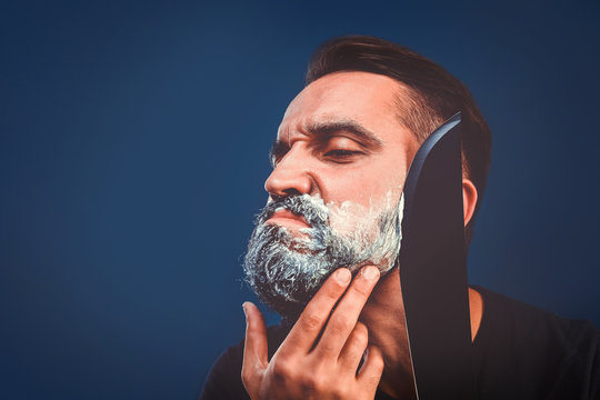 Barbershop background with brutal shaving with machete of bearded man.