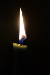 A green lit candle in the dark, the flame illuminating only toe top of the candle, the tip of the wick glowing.