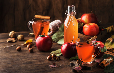 Hot mulled apple cider with with cinnamon sticks, cloves and anise on wooden background. Traditional autumn, winter drinks and cocktails