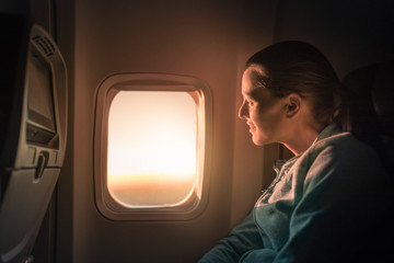 Young female smiling looking out airplane window at the sunrise. People traveling by airplane, transportation, vacation concept.