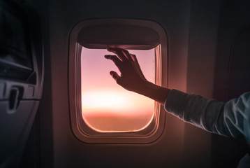 Female's hand opening airplane window at sunset. People traveling by airplane, transportation, vacation concept.