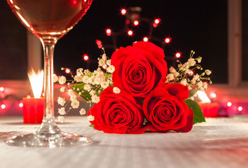 Wall Mural - closeup of red roses in a candle light dinner setting. . Beautiful romantic fine dinning setting.