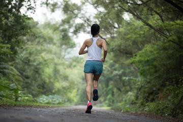 Fototapeta Female runner running at summer park trail . Healthy fitness woman jogging outdoors. obraz