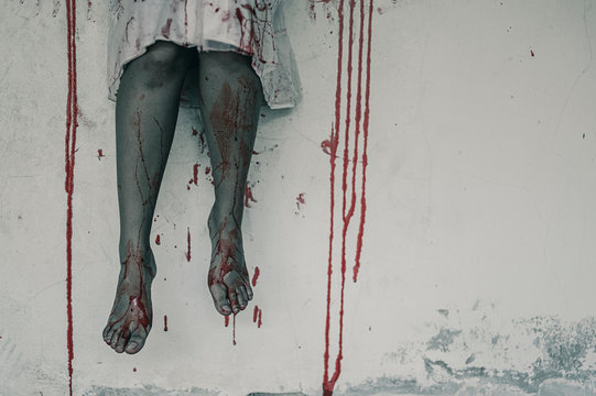 Horror Scene of a Woman with Bloody leg .Zombie woman sitting hanging legs on building is screaming darkness and nightmare horror of scary,  Halloween murder concept.