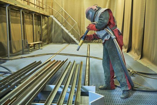 Sandblasting in chamber. Worker makes sand blast cleaning of metal detail