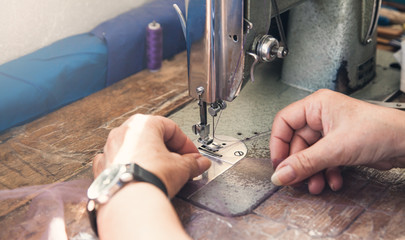 Caucasian seamstress working with sewing machine.