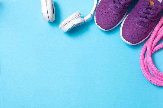 headphones, sneakers, jump rope on blue background flat lay