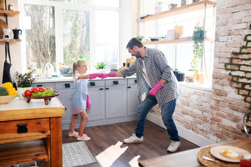 Obraz Girl feeling excited before cleaning kitchen with daddy - fototapety do salonu