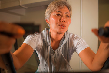 lifestyle portrait of middle aged attractive and happy Asian Indonesian woman with grey hair training exercise smiling at gym doing stationary bike workout sweaty
