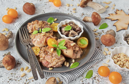 Chicken stuffed with wild mushrooms. Healthy homemade lunch or dinner - baked chicken, wild mushrooms, vegetables, pine nuts on a light background