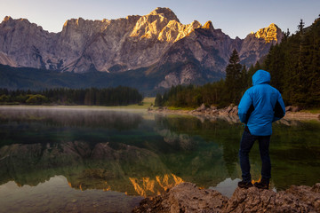 Fotomurales - traveler admiring the alpine lake during sunrise