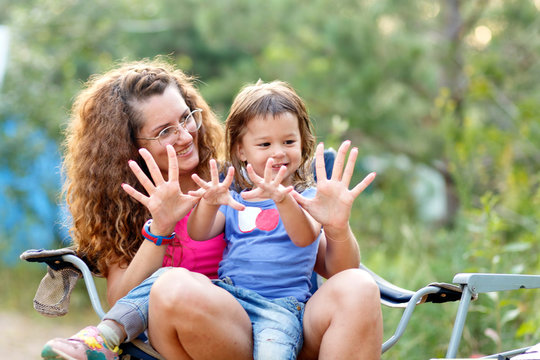Beautiful young moms with curly hair playing with a little daughter.