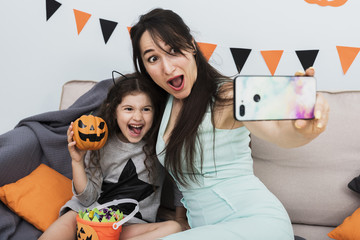 Mother taking a selfie with daughter on halloween