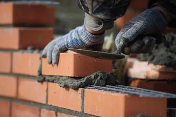 Brick wall contruction with mason hands