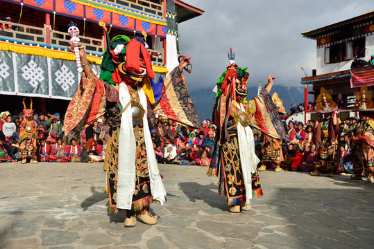 Tawang, Arunachal Pradesh, India, Buddhist monk dancing in disguise for the Torgya  festival, in the background there are monastery and many gathered viewers.
