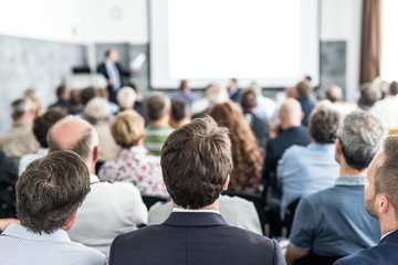 Wall Mural - Speaker giving a talk in conference hall at business event. Audience at the conference hall. Business and Entrepreneurship concept. Focus on unrecognizable people in audience.