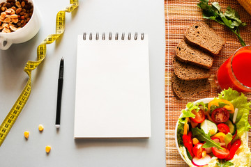 Diet sports nutrition, measuring tape and notebook with place for text. slimming concept