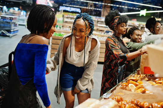 Group of african womans with shopping carts near baked products at a supermarket.