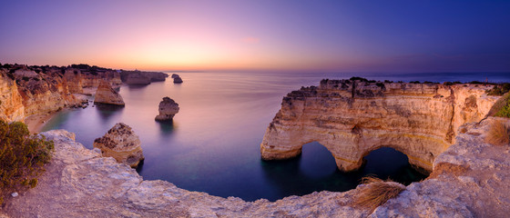Poster Coast Blue hour and sunrise along the Algarve coast towards Faro from the cliffs above Praia da Marinha, Portugal