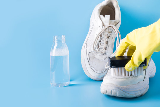 Dirty white sneakers with special tool for cleaning them on blue.