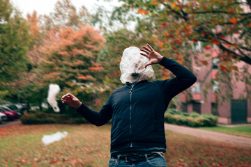 a man is hit in the face by a flying plastic bag while he walks in a park. pollution, ecology and green management concept