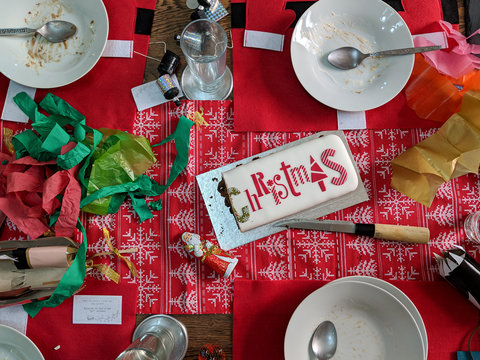 Leftover Christmas cake and empty plates on a messy table after the party. Overhead view.