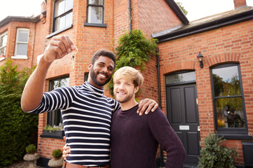 Portrait Of Excited Gay Male Couple Standing Outside New Home Holding Keys On Moving Day Together