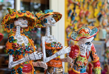 Traditional Mexican skulls, Calaveras, skeletons, La Muerte masks and other scary death symbols of the Day of the Dead, Dia de los Muertos, Halloween, popular souvenirs sold in Mexico.