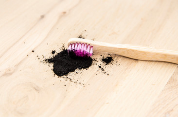 Raw activated charcoal powder on wooden background natural bamboo toothbrush inside it. Charcoal toothpaste concept. Minimalist composition with lot of copy space.