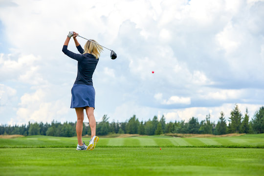 Portrait of a beautiful woman playing golf on a green field outdoors background. In full growth. Back vie. The concept of golf, the pursuit of excellence, personal excellence, royal sport.