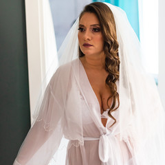 Woman in a transparent bridal robe waiting to try on her wedding dress. Graceful hairstyle, beauty make-up, white dress. Expressions, emotions in the wedding day.