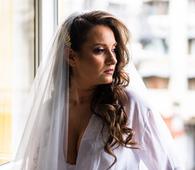 Bride in apartment in her wedding dress. Bride looks out of the window, waiting for her groom.