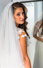 Bride looking in the mirror, getting ready for her wedding. Graceful hairstyle, beautiful make-up, white dress.