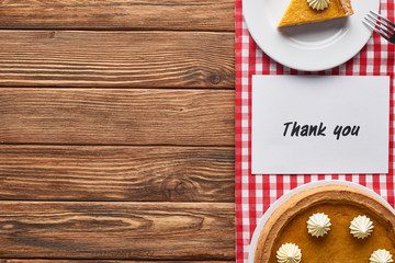 top view of pumpkin pie and thank you card on wooden brown table with red plaid napkin