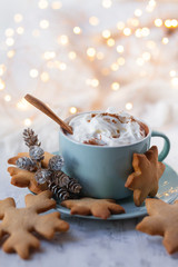 Hot winter drink: chocolate with whipped cream in blue mug. Christmas time. Cozy home atmosphere, white background. Homemade gingerbread cookies, cones, candle, lights as decor. Holiday festive mood