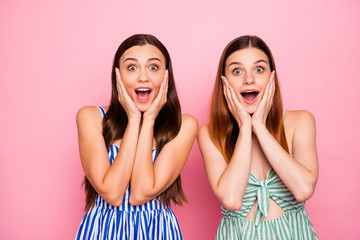 Portrait of impressed girls touching their face with hands shouting wearing striped dress skirt isolated over pink background