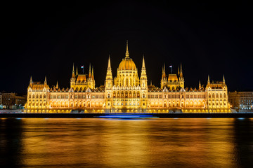 Illuminated historical building of Hungarian Parliament at night on Danube River Embankment