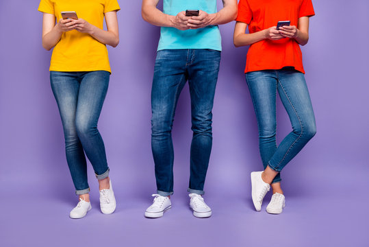 Cropped close up photo of three carefree teenagers user holding in hands and using digital gadgets wearing red blue and yellow outfit isolated violet background