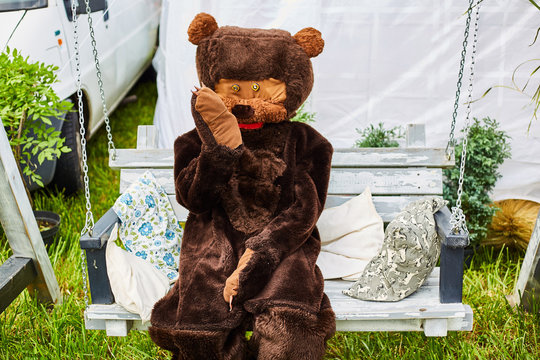 Man in a bear costume on holiday. Bear on a swing