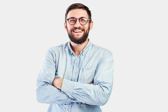 Friendly face portrait of an authentic caucasian bearded man with glasses of toothy smiling dressed casual against a white wall isolated