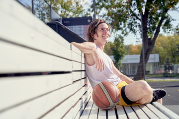 Picture of sporty man with volleyball ball sitting on wooden bench on summer.